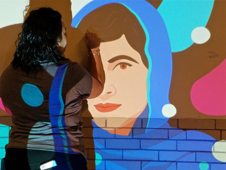 Anisa Shafiq uses a slide projector to mark out a mural of Malala Yousafzai in a hallway of Kensington High School.