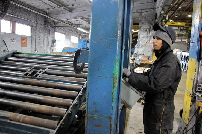Benjamin Ruiz of Camden operates machinery at Camden Yards Steel Company. (Emma Lee/WHYY)