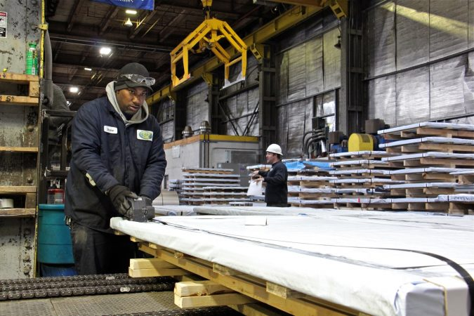 Workers prepare steel for shipment at Camden Yards Steel Company. (Emma Lee/WHYY)