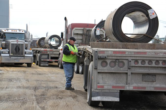 A trucker secures a heavy steel roll outside the Camden Yards Steel Company. (Emma Lee/WHYY)