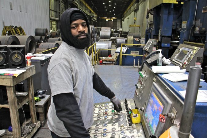 Isaac Pernell of Woodlynne, who started at Camden Yards five years ago in the packaging department, now operates a leveler, which straitens out the curled steel that arrives in rolls. (Emma Lee/WHYY)