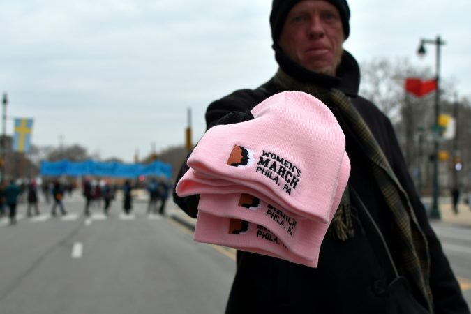 An unidentified sales person asks $10 for these hats commemorating the Women's March in Philadelphia, Pa., on January 19, 2019. (Bastiaan Slabbers for WHYY)