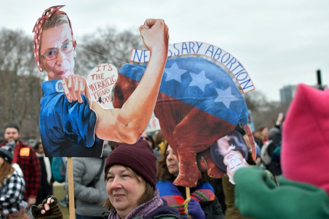 Creative signs are held up by participants during the 2019 Women's March, at Eakins Oval, in Philadelphia, Pa. (Bastiaan Slabbers for WHYY)