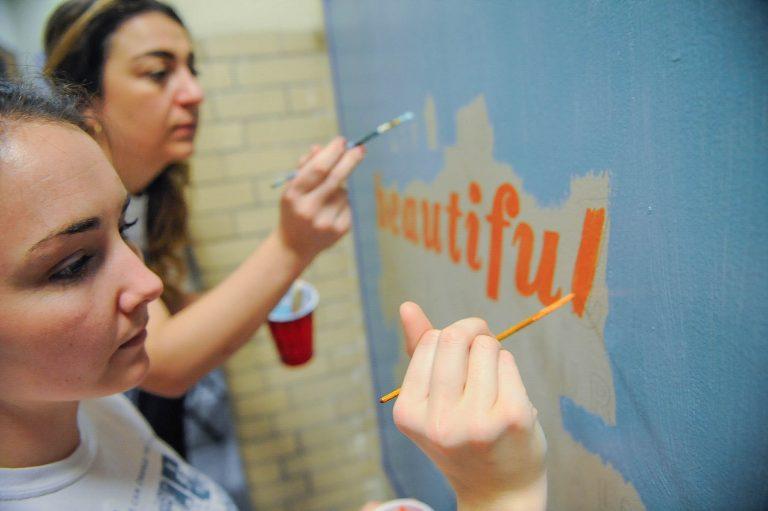 Kensington High School biology teacher Victoria Erickson (right) and her friend Megan Nardi, work on a mural on Kensington High School's ground floor.