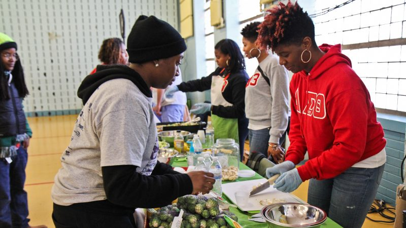 A volunteer at the Vetri Community funds demonstrates healthy cooking at the MLK Day of Service at Girard College. (Kimberly Paynter/WHYY)