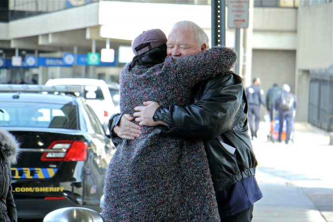 Alora Miller hugs Joe Shuker, president of the local American Federation of Government Employees, after she dropped off a load of donated supplies for TSA workers at Philadelphia International Airport. (Emma Lee/WHYY)