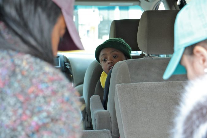 Alora Miller's son, Kevin, watches from his car seat as his mother and her friend, Allyson Bremme, unload donated goods for TSA employees at Philadelphia International Airport. (Emma Lee/WHYY)