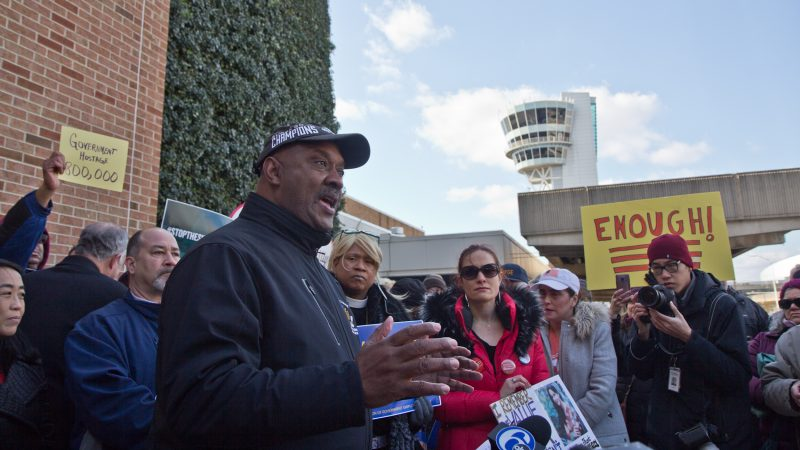 U.S. Congressman Dwight Evans calls for an end to government shutdown outside Philadelphia International airport Friday. (Kimberly Paynter/WHYY)