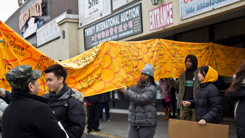 Members and supporters of Philadelphia's Southeastern Asian community carry a history dragon to protest deportations at a shopping center on West Oregon Avenue on Sunday, Jan. 27, 2019. (Kimberly Paynter/WHYY)