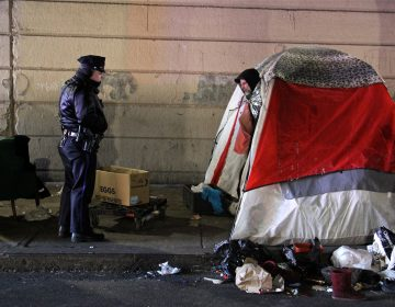 A Philadelphia police officer moves from tent to tent telling residents of the Emerald Street encampment that it's time to go. (Emma Lee/WHYY)