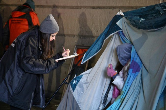 An outreach worker gets information from a woman living in a tent under the Emerald Street railroad overpass. (Emma Lee/WHYY)