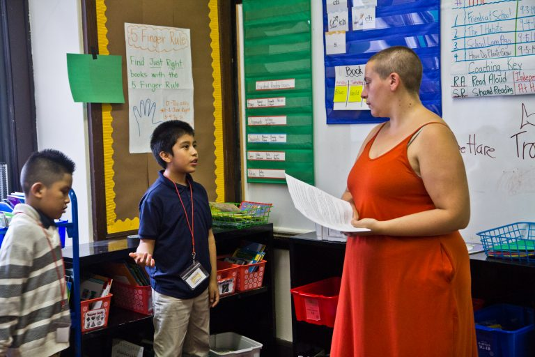 A third-grade student explains to Isy Abraham-Raveson about why he chose the green light on behavior during a consent workshop. (Kimberly Paynter/WHYY)