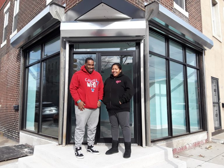 Al Harris, left, and Marjani 'MJ' Harris, right, stand outside the new CancerWho? community center in the Port Richmond neighborhood. (Trenae Nuri/WHYY News)