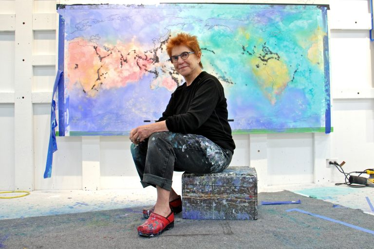 Artist Diane Burko poses in front of an unfinished work at her Center City studio.