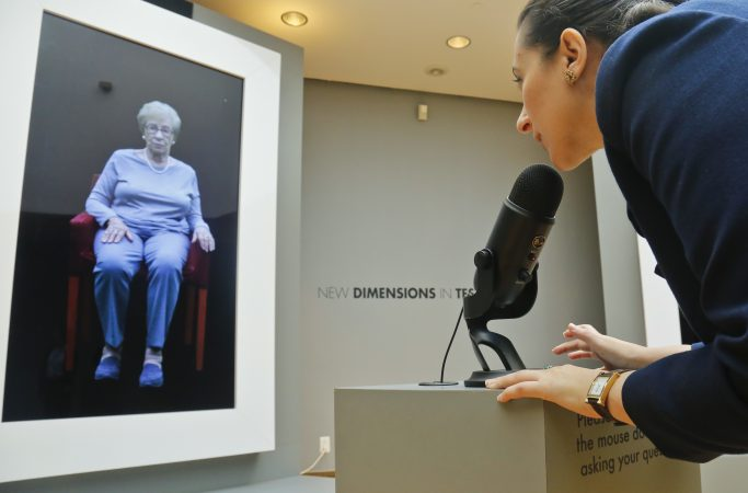 In this Friday Sept. 15, 2017, photo, Josephine Mairzadeh, (right), use a microphone to pose a question to a virtual presentation of Holocaust survivor Eva Schloss, (left), featured in a testimonial interactive installation called