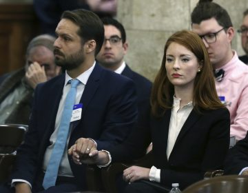 In this file photo, Katie Brennan, the chief of staff at the New Jersey Housing and Mortgage Finance Agency, holds hands with her husband Travis Miles as she waits to testify before the Select Oversight Committee at the Statehouse, Tuesday, Dec. 4, 2018, in Trenton, N.J. (Mel Evans/AP Photo)