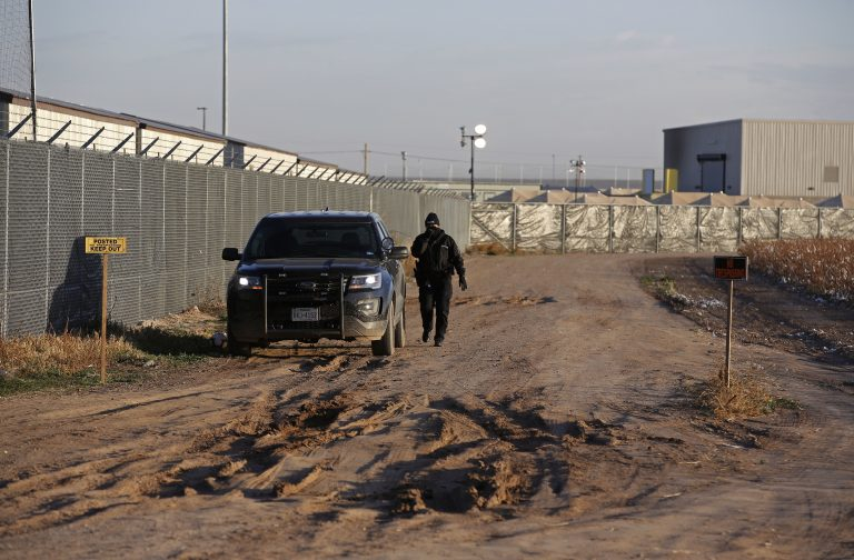 In this file photo, a private security guard patrols outside the Tornillo detention camp for migrants in Tornillo, Texas, Thursday Dec. 13, 2018. (Andres Leighton/AP Photo)