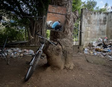 In this Dec. 14, 2018 photo, a mirror tied to a tree reflects a heroin user preparing his dose, in an area popular for people with a drug addiction behind an abandoned home in Humacao, Puerto Rico. Heroin users will often use the mirror to get a better view of themselves when injecting, especially when into their necks. (AP Photo/Carlos Giusti)