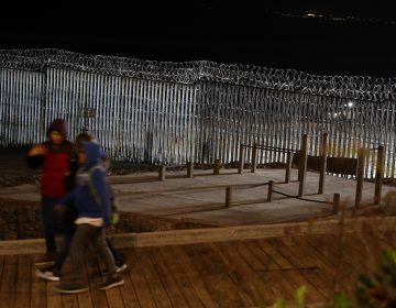 Floodlights from the U.S, illuminate the border wall, topped with razor wire, as a people pass Monday, Jan. 7, 2019, at the beach in Tijuana, Mexico. With no breakthrough in sight, President Donald Trump will argue his case to the nation Tuesday night that a