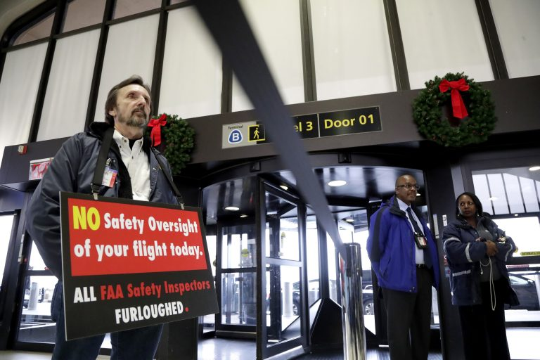 Federal Aviation Administration employee Michael Jessie, who is currently working without pay as an aviation safety inspector for New York international field office overseeing foreign air carriers, holds a sign while attending a news conference at Newark Liberty International Airport, Tuesday, Jan. 8, 2019, in Newark, N.J. U.S. Sens. Cory Booker and Bob Menendez called a news conference at the airport to address the partial government shutdown, which is keeping some airport employees working without pay. (Julio Cortez/AP)