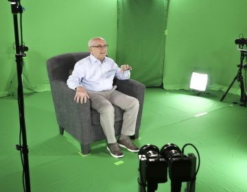 This August 2018 photo shows Holocaust survivor Max Glauben sitting in an interactive green screen room while filming a piece for the Dallas Holocaust Museum in Dallas. (McGuire Boles/Dallas Holocaust Museum via AP)