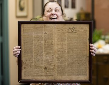 In this Thursday, Oct. 25, 2018 file photo, Heather Randall displays a Dec. 28, 1774 Pennsylvania Journal and the Weekly Advertiser at the Goodwill Industries South Jersey in Bellmawr, N.J.  An original 1774 Philadelphia newspaper that was discovered at a New Jersey Goodwill is heading to a Philadelphia philosophy society founded by Benjamin Franklin. (Matt Rourke/AP)