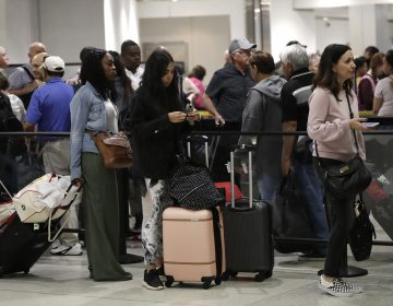 In this Jan. 18, 2019, file photo passengers wait in line at a security checkpoint at Miami International Airport in Miami. While security screeners and air traffic controllers have been told to keep working, Federal Aviation Administration safety inspectors weren't, until the agency began recalling some Jan. 12. About 2,200 of the more than 3,000 inspectors are now back on the job, overseeing work done by airlines, aircraft manufacturers and repair shops. The government says they're doing critical work but forgoing such tasks as issuing new pilot certificates. (Lynne Sladky, AP)