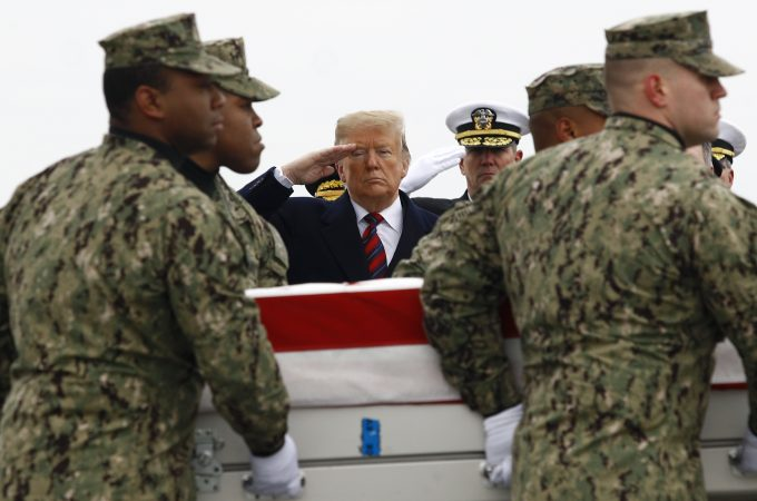 President Donald Trump salutes as a U.S. Navy carry team moves a transfer case containing the remains of Scott A. Wirtz, Saturday, Jan. 19, 2019, at Dover Air Force Base, Del. According to the Department of Defense, Wirtz, a civilian and former Navy SEAL from St. Louis, Mo., was killed Jan. 16, 2019, in a suicide bomb attack in Manbij, Syria. (Patrick Semansky/AP Photo)