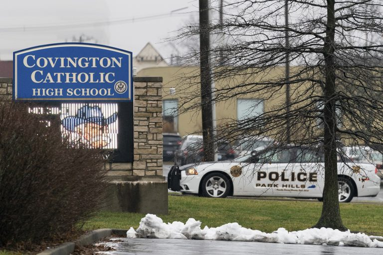 A police car sits at the entrance to Covington Catholic High School in Park Hills, Ky., Saturday, Jan 19, 2019. A diocese in Kentucky apologized Saturday after videos emerged showing students from the Catholic boys' high school mocking Native Americans outside the Lincoln Memorial on Friday after a rally in Washington. (AP Photo/Bryan Woolston)