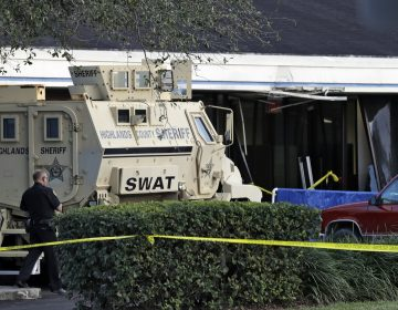 A Sebring, Fla., police officer stands near a Highlands County Sheriff's SWAT vehicle that is stationed in front of a SunTrust Bank branch, Wednesday, Jan. 23, 2019, in Sebring, Fla., where authorities say five people were shot and killed. (Chris O'Meara/AP Photo)