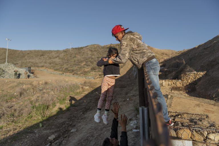 In this Jan. 3, 2019, file photo, a migrant from Honduras pass a child to her father after he jumped the border fence to get into the U.S. side to San Diego, Calif., from Tijuana, Mexico. The Trump administration expects to launch a policy as early as Friday, Jan. 25, that forces people seeking asylum to wait in Mexico while their cases wind through U.S. courts, an official said, marking one of the most significant changes to the immigration system of Donald Trump's presidency. (Daniel Ochoa de Olza, AP Photo)