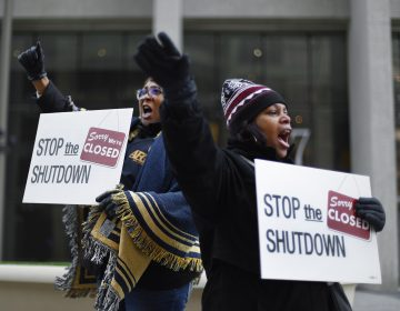 In this Jan. 10, 2019 file photo Cheryl Monroe, (right), a Food and Drug Administration employee, and Bertrice Sanders, a Social Security Administration employee, rally to call for an end to the partial government shutdown in Detroit. The government shutdown left an especially painful toll for African-Americans who make up nearly 20 percent of the federal workforce and historically have been on the low end of the government pay scale. (Paul Sancya/AP Photo, file)