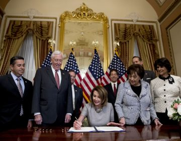 House Speaker Nancy Pelosi of Calif., center, accompanied by from left, Rep. Ben Ray Lujan, D-N.M., House Majority Leader Steny Hoyer of Md., Rep. Nita Lowey, D-N.Y, Rep. Lucille Roybal-Allard, D-Calif., and others, signs a deal to reopen the government on Capitol Hill in Washington, Friday, Jan. 25, 2019. he measure now goes to the White House for President Donald Trump to sign.  (AP Photo/Andrew Harnik)