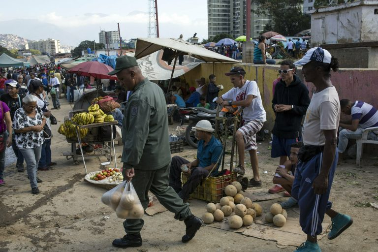 Workers and customers gather at a wholesale food market in Caracas, Venezuela, Monday, Jan. 28, 2019. Economists agree that the longer the standoff between the U.S.-backed opposition leader Juan Guaido and President Nicolas Maduro drags on, the more regular Venezuelans are likely to suffer. (AP Photo/Rodrigo Abd)