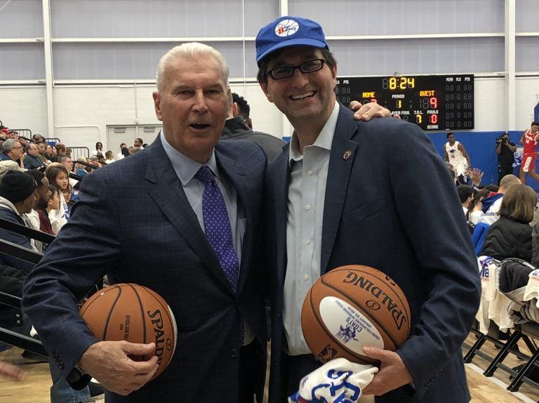 Wilmington Mayor Mike Purzycki (left) and New Castle County Executive Matt Meyer were all smiles Wednesday night at opening night for the Delaware Blue Coats at the city's new sports and concert facility, but are locked in a dispute over the thorny and expensive issue of property tax reassessment. (Cris Barrish/WHYY)