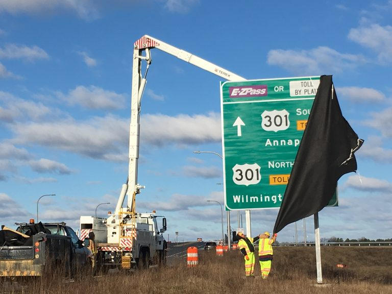 Workers unveil signs directing drivers to the new Route 301 near Middletown. (Mark Eichmann/WHYY)