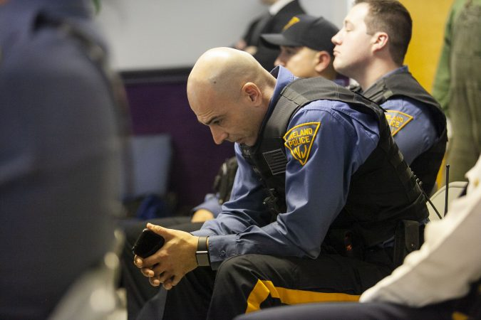 Vineland Police Officer Luis Rivera look down as audience members offer their remarks about policing . Gurbir S. Grewal and Jennifer Webb-McRae host community listening session on Police use fo force on Jan. 23, 2019. (Miguel Martinez for WHYY)during a community listening session in Bridgeton, N.J., Jan. 23, 2019. (Miguel Martinez for WHYY)