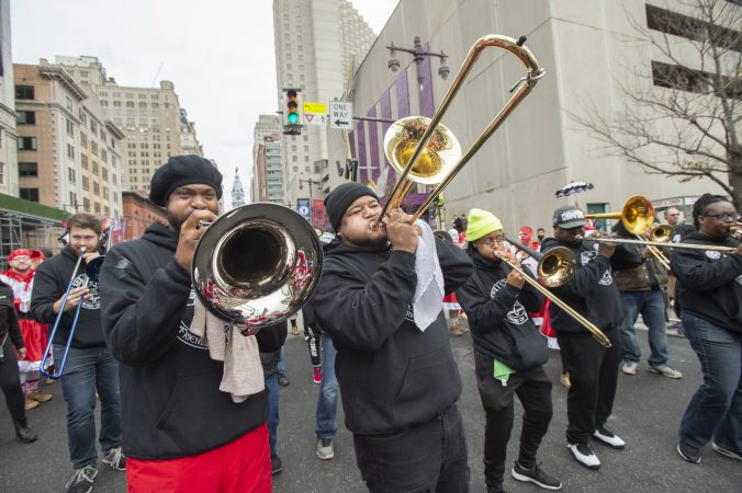 The brass band of the Wench's Cara Liom play Sweet Caroline while brigade members dance. (Jonathan Wilson for WHYY)