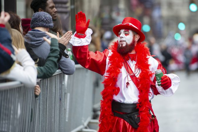 Michael Caukin a member of the Wench Division's Cara Liom high fives the spectators on Broad St.(Jonathan Wilson for WHYY)
