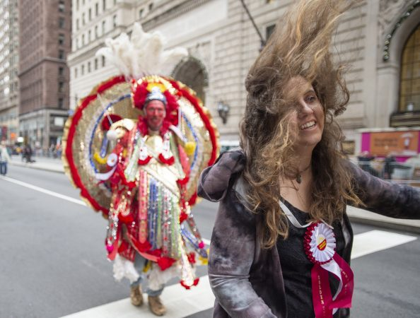 Amber Hawk's hair covers her face as she heads into wind gusts on Broad St. She is a member of the Fancy Division's Golden Sunrise.(Jonathan Wilson for WHYY)