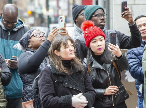 Crowds hold their phones aloft at Broad and Walnut Streets. (Jonathan Wilson for WHYY)
