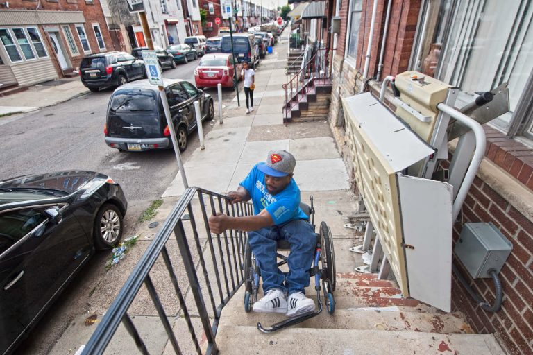 Rodney Whitmore of South Philadelphia was shot and paralyzed in 1995. When his wheelchair lift is broken, he tilts his wheelchair backward and lowers himself down his front steps so he can get to work.