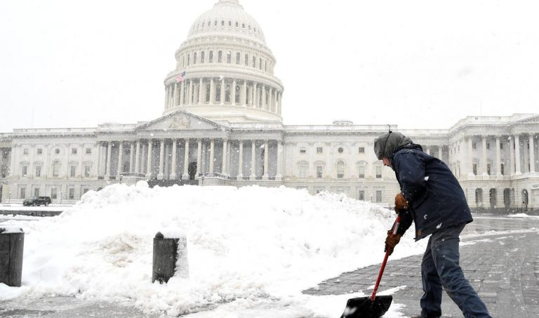 Aaron Rowe of the Architect of the Capitol's office, which is not affected by the partial government shutdown, shovels snow left by a winter storm on the U.S. Capitol's plaza.  (REUTERS/Mike Theiler)