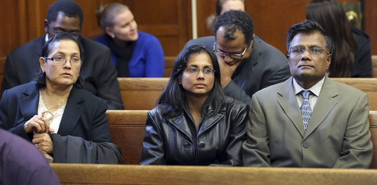 Annie Dookhan, (center), pictured with her family in a Boston courtroom Nov. 22, 2013, after she pleaded guilty to tampering with evidence. Dookhan was a state chemist. (David L. Ryan/AP/The Boston Globe)