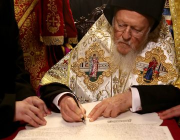 Bartholomew I signs the Tomos of Autocephaly, marking the formal independence of the Ukrainian Orthodox Church at the Patriarchal Church of St. George, in Istanbul. (Anadolu Agency/Getty Images)