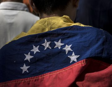 An attendee wears a Venezuelan flag during a rally in Caracas Friday with Juan Guaido, president of the National Assembly, who swore himself in as the leader of Venezuela. (Marcelo Perez del Carpio/Bloomberg via Getty Images)