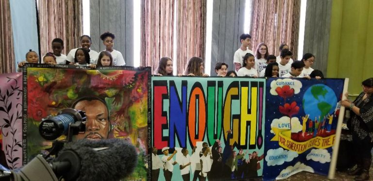 Students hold up mural created for King Day of Service. (Tom MacDonald/WHYY)