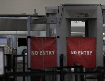 Travelers are permitted from entering a closed down terminal at the Miami International Airport on Saturday, Jan. 12, 2019, in Miami. The partial government shutdown is starting to strain the national aviation system, with unpaid security screeners staying home, air-traffic controllers suing the government and safety inspectors off the job. (Brynn Anderson/AP Photo)