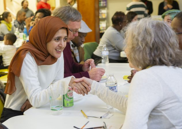 Suad Monee introduces herself to a fellow attendee at Uneven Play: A Community Dinner and Conversation held at St Pauls Lutheran Church in Olney. (Jonathan Wilson for WHYY)