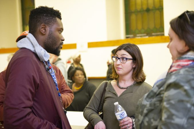 Members of non-profit Playworks, (from left) Dontae Privette, Ivy Olesh, and Corrie O'Neil, talk after Uneven Play: A Community Dinner and Conversation. (Jonathan Wilson for WHYY)